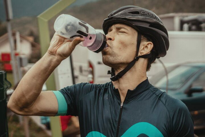 cyclist drinks from water bottle
