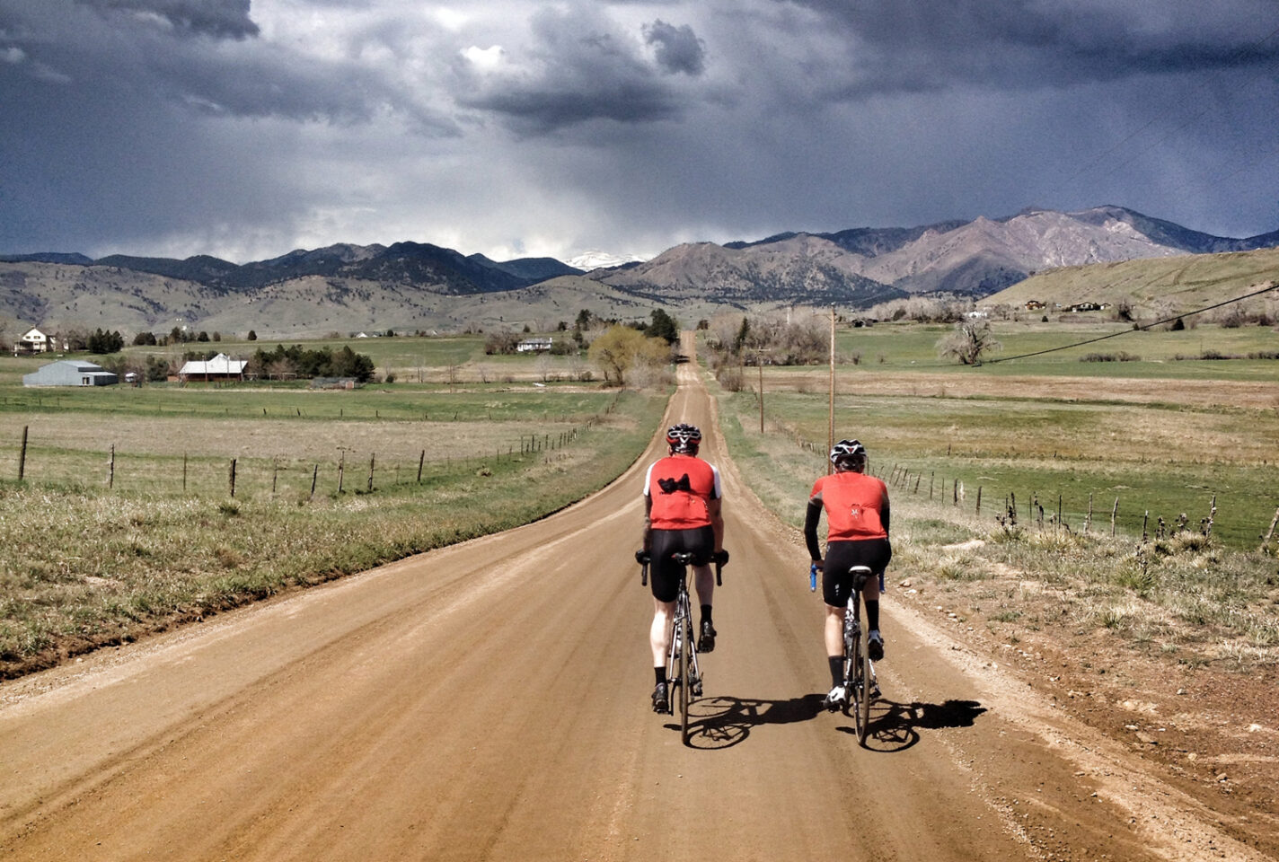 Two cyclists ride into the distance on dirt roads in North Boulder, Colorado.